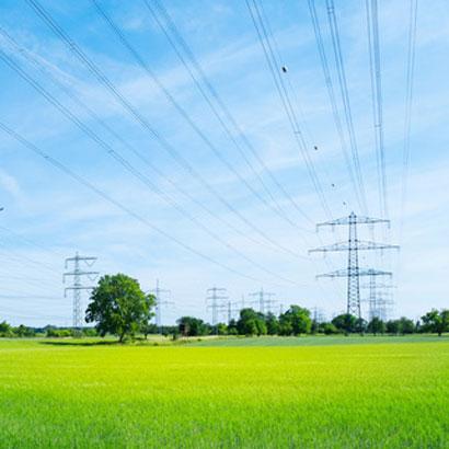 Grüne Landschaft mit Strommasten und Stromleitungen