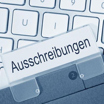 Ordner mit Register Auschreibungen liegt auf einer Tastatur