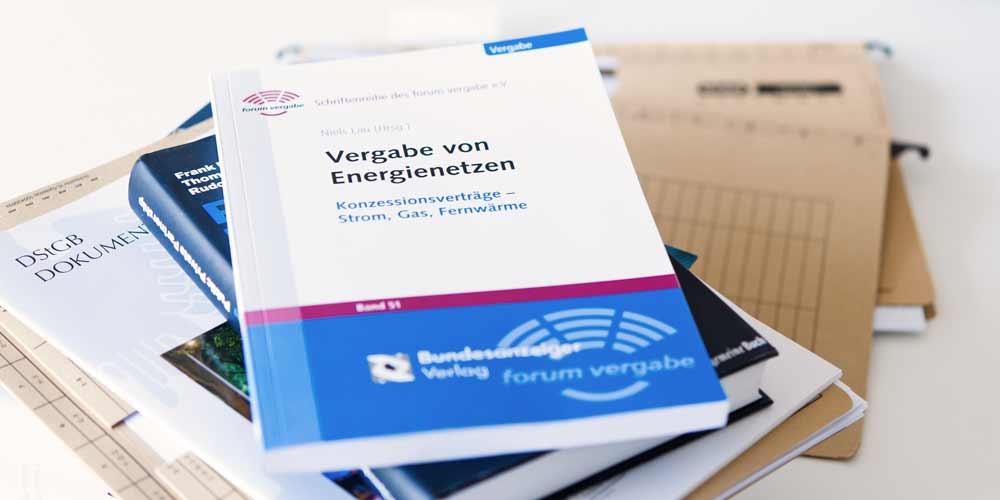 Abbildung eines Stapels von Büchern und Dokumenten zum Thema Energierecht