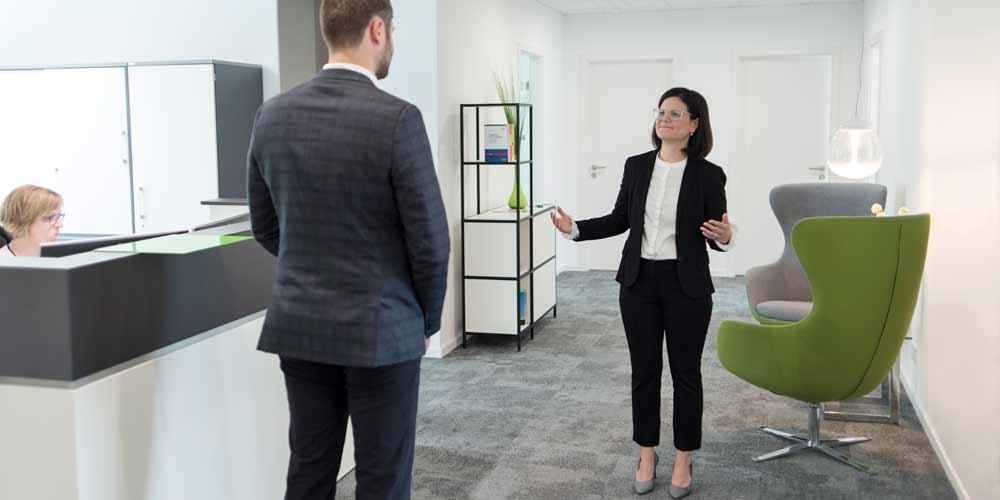 Dr. Desiree Jung empfängt einen Klienten im EIngangsbereich mit Anmeldetresen in ihrer Kanzlei