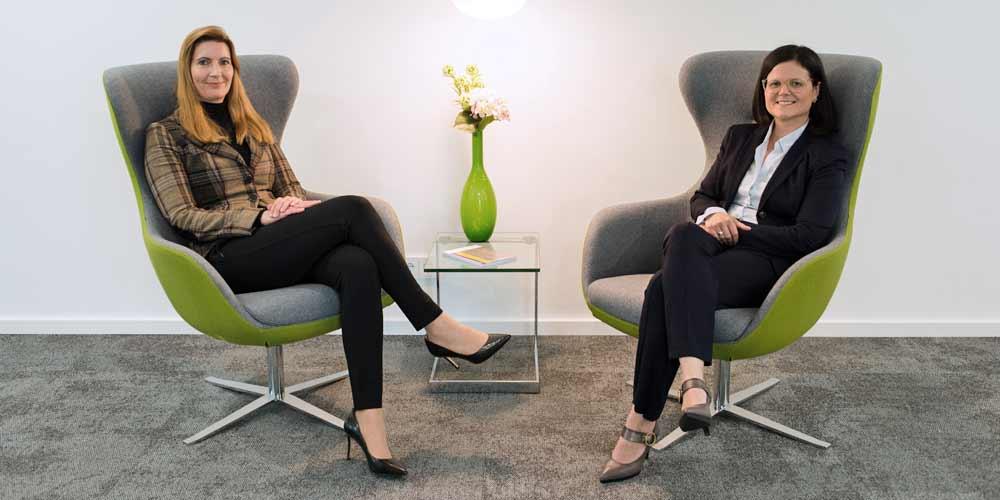 Dr. Desiree Jung und Rechtsanwältin Andrea Heim sitzen sich beim Gespräch in zwei Loungeseseln in der Kanzlei gegenüber